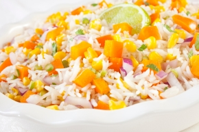 A beautiful rice salad with orange capsicum, yellow corn, red onion and green onion and garnshed with lime.