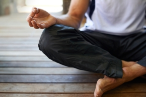 Cropped view of a man doing yoga in the lotus position