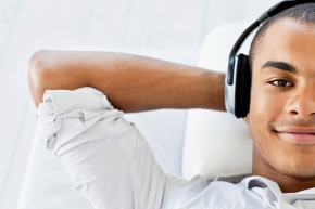 A handsome young man is lying down and listening to headphones as he smiles at the camera.  Horizontal shot.