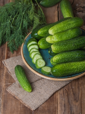 Fresh cucumbers  and slices on a wooden table
