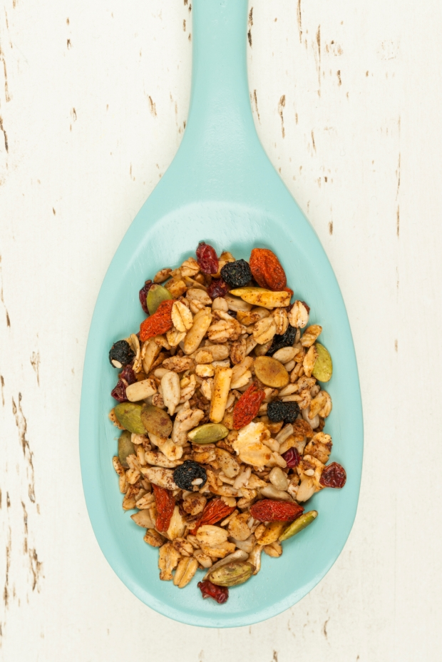 Homemade granola with various seeds and berries in wooden spoon shot from above