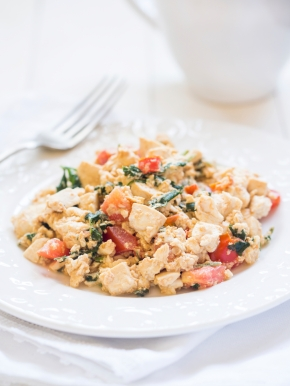 Vegan tofu scramble with tomato and green herbs. White background, vertical orientation, close up.